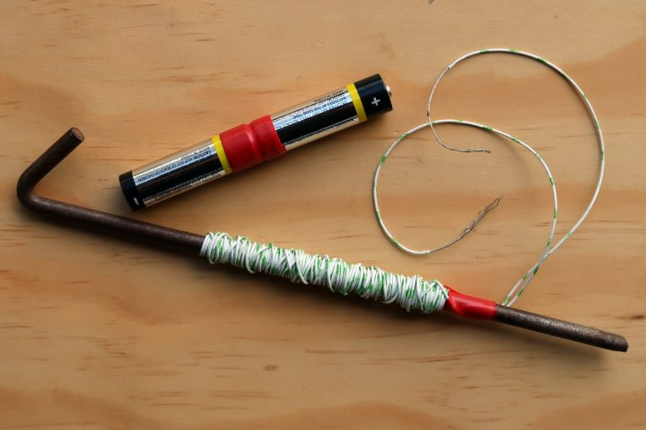 A tent peg wrapped with thin insulated wire and 2 AA batteries joined together with tape