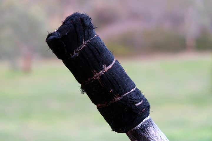 a used fire torch with the cloth outer charred but intact