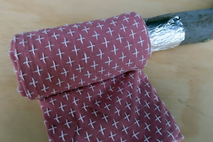 a magenta tea towel being wrapped around the end of a wooden stick