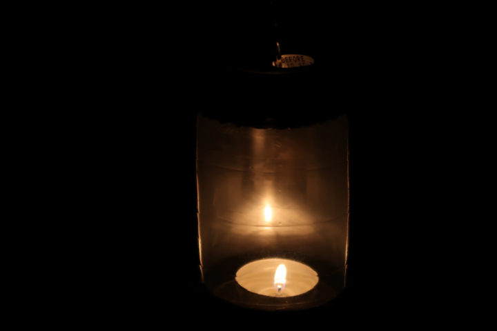 close-up of candle burning in a soda can lantern
